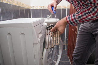 a young repairman with a screwdriver repairs an old heating element or a teng from a faulty washing machine. Washing machine repair